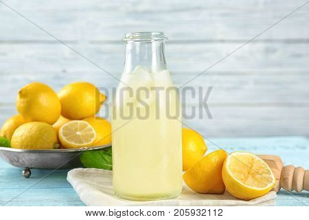 Composition with bottle of lemon juice and fresh lemons on wooden table