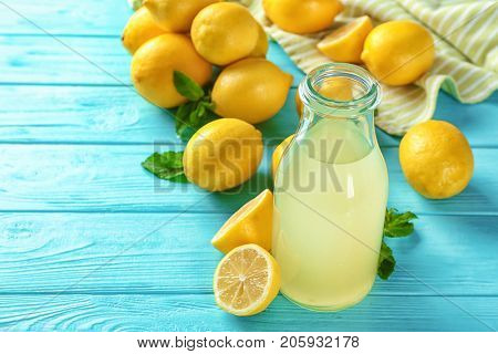 Bottle of lemon juice and fresh lemons on table