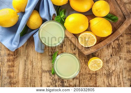 Glasses of lemon juice and fresh lemons on wooden table