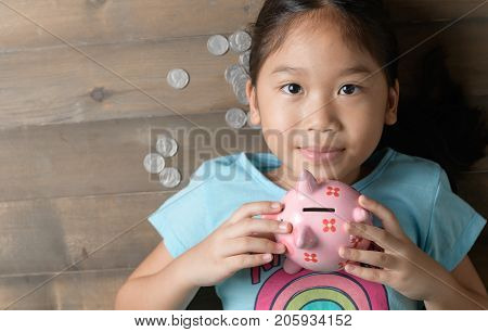 Cute Girl Hold A Pig Bank On The Vintage Wood Background