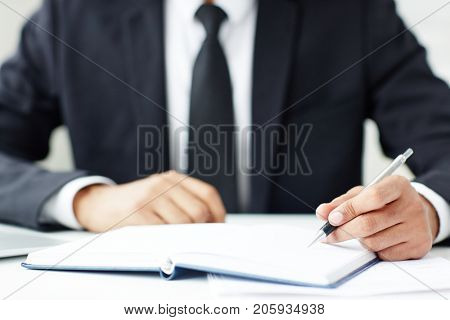 Manager in formalwear writing down agenda points in notebook