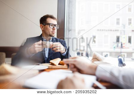 Young man in suit and eyeglasses drinking tea at lunch break in cafe and looking through window