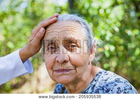 Smiling elderly female portrait in the garden doctor's hand on forehead