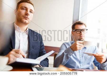 Attentive businessman with notepad making notes and listening to someone