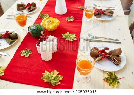 Glasses with juice, silverwear, candles and cucurbits on festive table decorated with green leaves