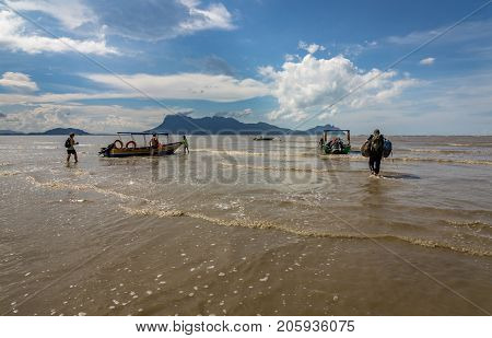 People walking and wading into the water to get to the boats at the beach of Bako National Park in Sarawak, Kuching, Borneo, Malaysia