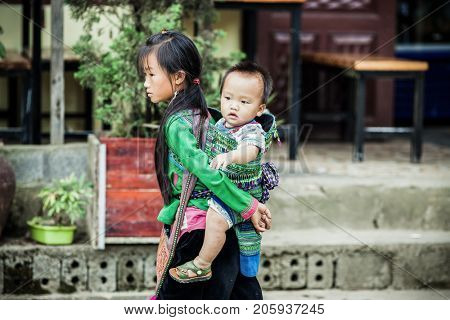 SA PA, VIETNAM - AUGUST 2017: Black hmog ethnic minority girl carrying child in Sa Pa town, the high mountains, Lao Cai province, Vietnam