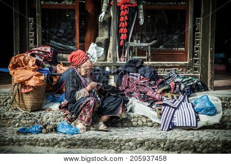 SA PA, VIETNAM - AUGUST 2017: Red dzao ethnic minority woman sewing in Sa Pa, Lao Cai province, Vietnam