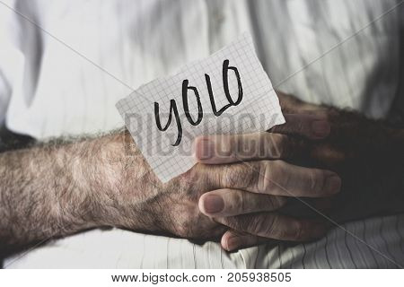 closeup of an old caucasian man with a note in his hands with the word yolo, for you only live once, written in it
