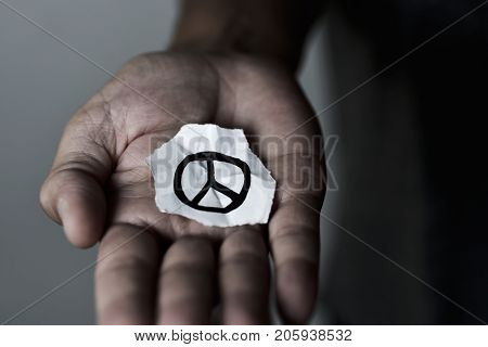 closeup of a young man with a piece of paper with a peace symbol drawn in it, in the palm of his hand