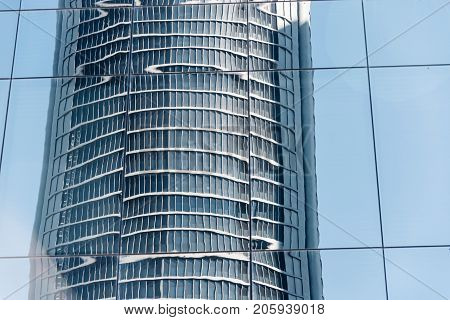 Madrid, Spain - June 25, 2017: Low angle view of reflections of skyscrapers in Cuatro Torres Business Area, CTBA Four Towers Business Area a business district in Madrid against blue sky