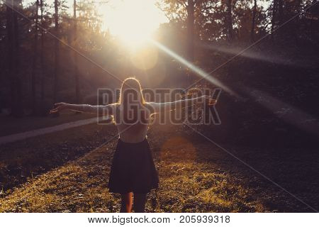 Woman Feeling Free On Sunset. Silhouette Of The Woman Spreading Arms With Her Thumbs Up, Standing In