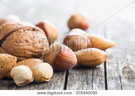 Different types of nuts in the nutshell. Hazelnuts, walnuts, almonds, pecan nuts and pistachio nuts on old wooden table.