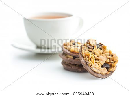 Chocolate chip cookies with nuts and raisins. Cookies with cup of tea isolated on white background.