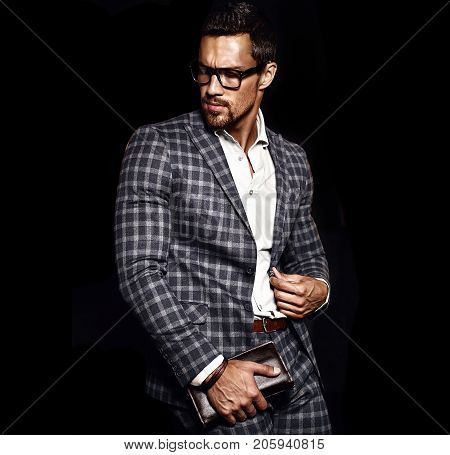 portrait of sexy handsome fashion male model man dressed in elegant suit on black background