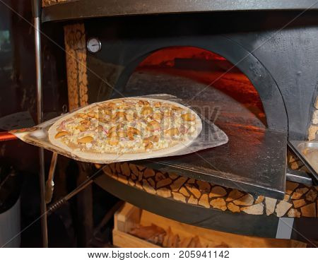 Baking mushroom pizza in traditional wood-fired Italian oven