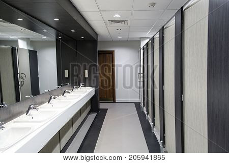 Public bathroom. Ladies restroom with cubicles and sinks in a hygienic senario. No people.