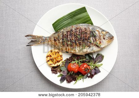 Plate with delicious fried fish on table