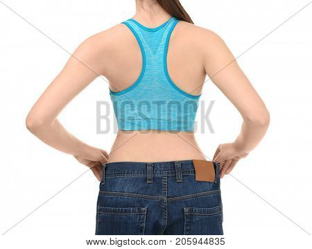 Young woman in oversized jeans on white background. Diet concept