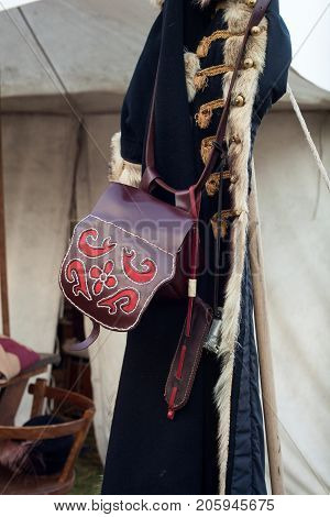 Embroidered bag and ancient coat hanging on pole during the historical Reenactment