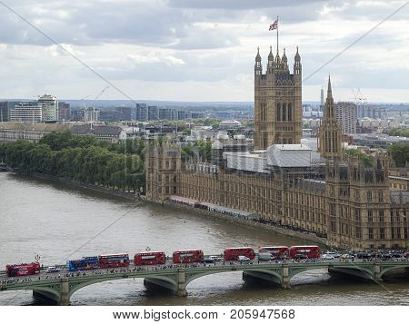 London, UK: July 25, 2016: The Houses of Parliament in London with red double decker buses crossing the bridge over the river Thames