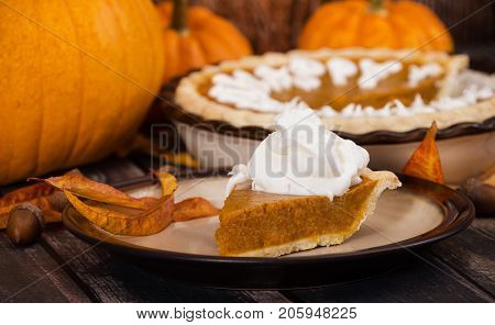 A slice of a pumpkin pie served with whipped cream. Pumpkins and autumn decorations diplayed on rustic table.