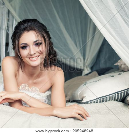Fashion Portrait of Glamorous Woman in White Vintage Bedroom. Smiling Model on White Interior
