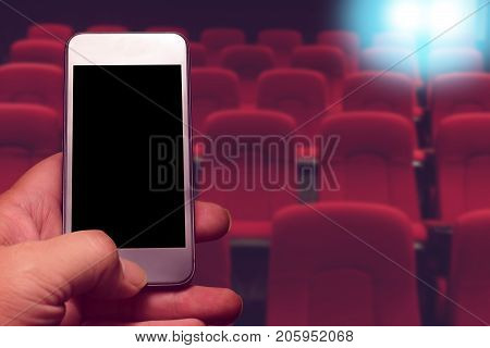 hand holding smartphone with black screen and row of red seat background. online ticket buying concept.