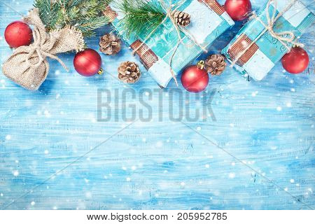 Top view of Christmas background on blue wooden board with fir red decorations snow and gift boxes forming top rim. Copy space.