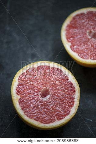 Closeup of grapefruit slices on black table