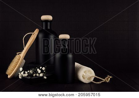 Cosmetics mock up - blank black bottles bath accessories white flowers on dark wood board copy space. Template for advertising designers branding identity cover.