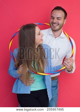 portrait of happy couple with hula hoop isolated on red background