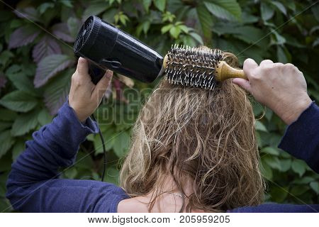 Woman drying her long hair with a hair dryer a foliage in the blurred background