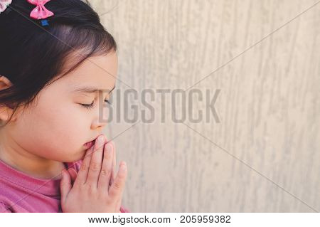 little multiethnic girl praying kid child pray conceptshallow DOF