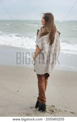 Fashion woman walking alone on a sea beach, casual oversize cloth, autumn outdoor