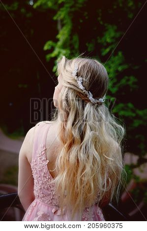 Portrait of a beautiful bride blond girl in pink lace dress , hair decoration, handmade. Tenderness. Rear view, focus on the hair