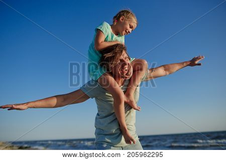 Young man gaily spends time with the little daughter by the sea. Girl of 8-9 years sits on shoulders at the father and cheerfully smile. Against the background of the blue sky.