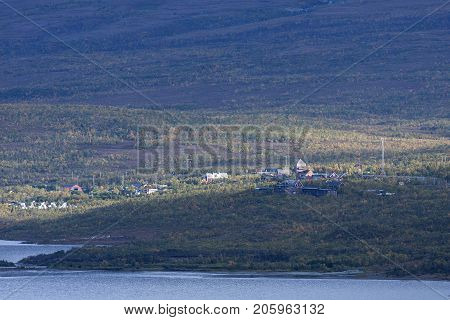 Rural village, community in afternoon sun. Taiga forest, mountain in the surrounding, autumn, fall.