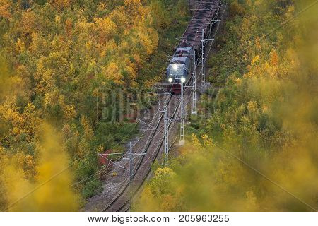 IRON ORE LINE, SWEDEN ON SEPTEMBER 13. View of a train pass through the colorful landscape on September 13, 2017 along the Iron Ore Line, Sweden. Train, railroad and forest. Editorial use.