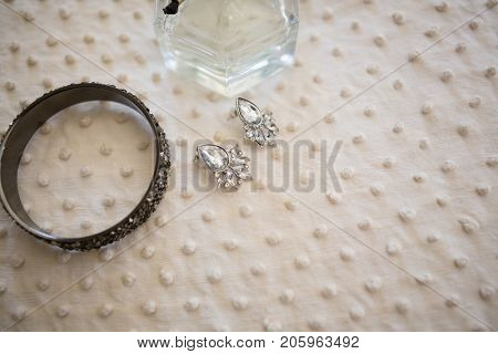High angle close up of earring with bangle and perfume bottle in dressing room