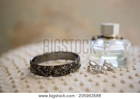 Close up of earring with bangle and perfume bottle in dressing room