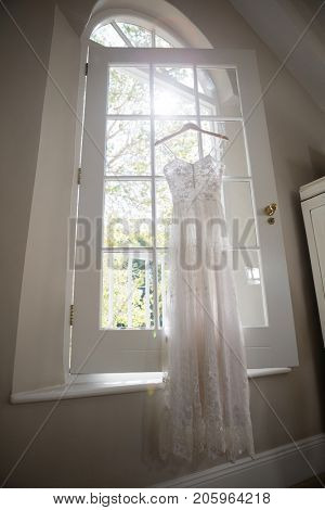 Wedding dress hanging on window in dressing room