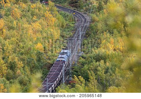 IRON ORE LINE, SWEDEN ON SEPTEMBER 11. View of a train pass through the colorful landscape on September 11, 2017 along the Iron Ore Line, Sweden. Train, railroad and forest. Editorial use.
