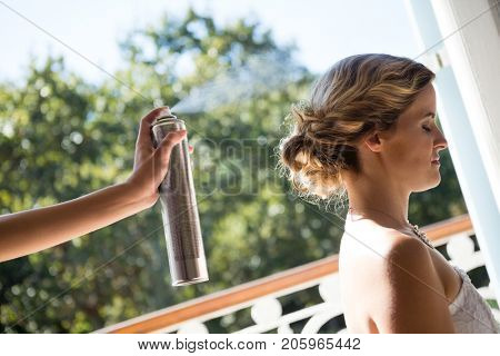 Cropped hand of bridesmaid applying hairspray to bride in dressing room