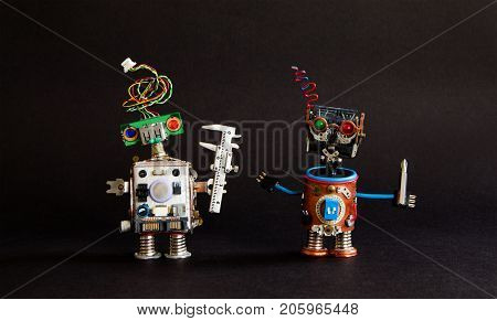 Industry 4.0 automation technology concept. Robot engineer caliper, cyborg handyman screwdriver. Creative design mechanic toy workers on black background