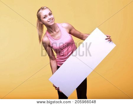 Young happy woman portrait of a confident businesswoman showing presentation, pointing placard yellow background. Ideal for banners, registration forms, presentation, landings, presenting concept.