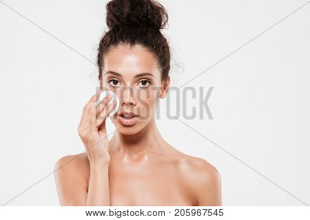 Beauty portrait of a young brunette woman with soft healthy skin removing make up with cotton pad isolated over white background
