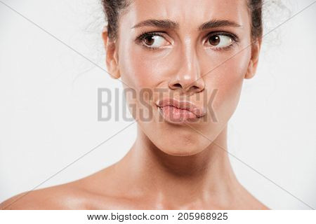 Cropped close up beauty portrait of a pensive doubting woman with soft healthy skin looking away isolated over white background
