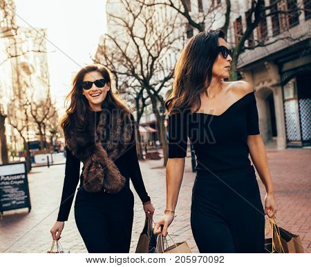 Female Friends Walking On The City Street With Shopping Bags