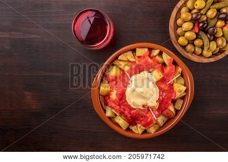 Overhead photo of traditional Spanish tapas. Pickled olives, patatas bravas, potatoes with red and white sauce, with a glass of wine, shot from above on a dark rustic texture